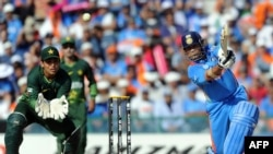 Pakistan wicketkeeper Kamran Akmal (left) looks on as Sachin Tendulkar hits a boundary during the Cricket World Cup semifinal between India and Pakistan in 2011. India went on to win the tournament.