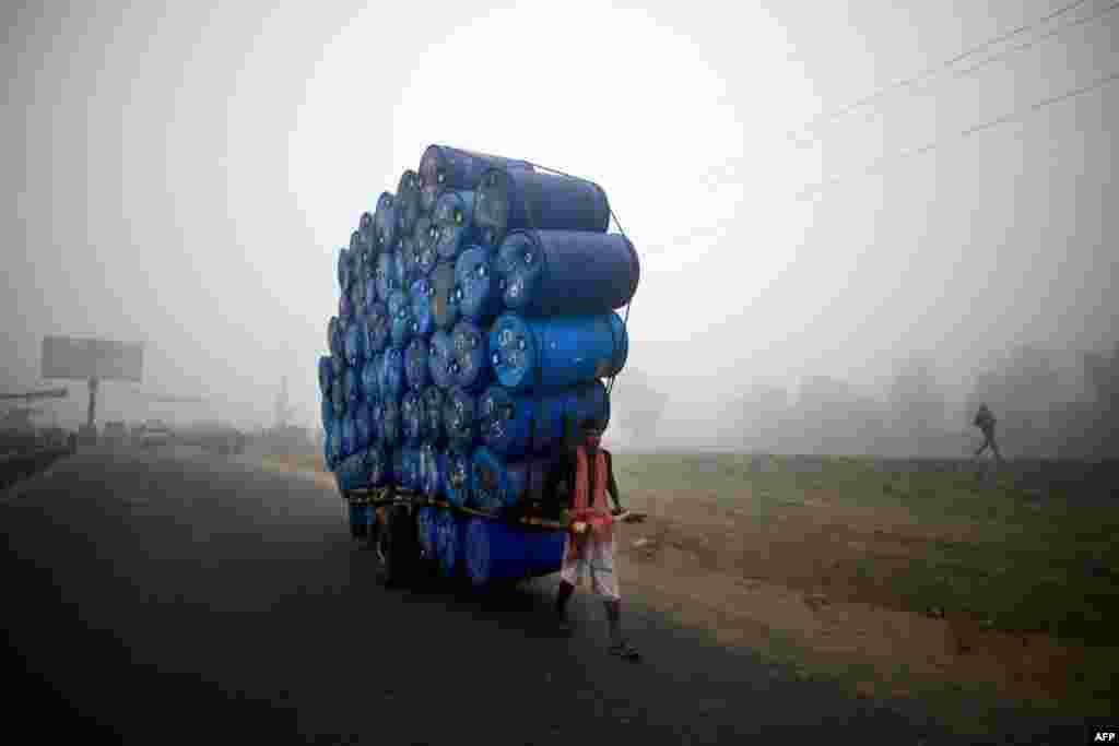 A Bangladeshi laborer pulls a cart full of empty drums during a nationwide strike in Dhaka. Twelve like-minded Islamic parties called an eight-hour general strike in the capital and a dawn-to-dusk general strike across the country as they seek a ban on left-wing political parties. (AFP/Munir uz Zaman)