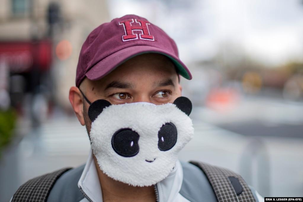 Футболист Алан Гордон надевает маску для лица в виде панды, отправляясь 1 апреля в Вашингтон, округ Колумбия, за едой.