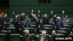 IRAN -- Iranian lawmakers rais their hands to vote during a parliamentary session in Tehran, January 7, 2020