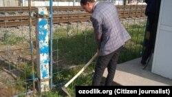 Преподаватель Гульбахорского промышленного профессионального колледжа убирает территорию железнодорожного переезда.