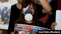 یکی از معترضان علیه سیاستهای نزدیک به پکن با پلاکاردی که عکس از مجروحان بر آن دیده میشود. روی پلاکارد نوشته شده «پلیس هنگکنگ به سر معترضان شلیک میکند».