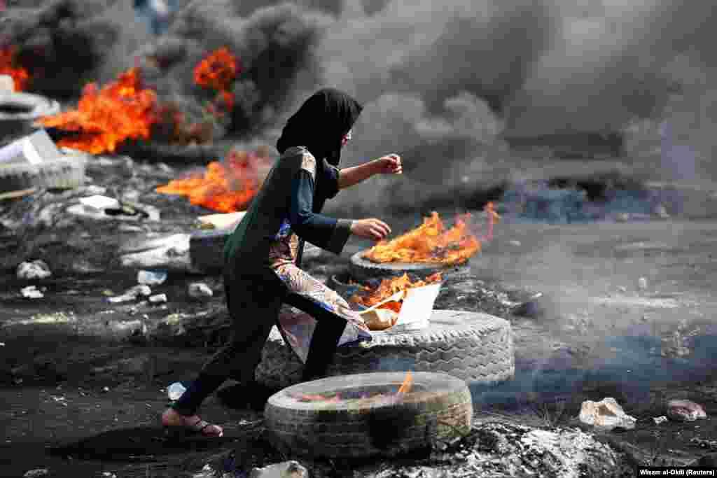 Дэманстрантка бяжыць паміж падпаленымі шынамі падчас пратэстаў у Багдадзе, Ірак