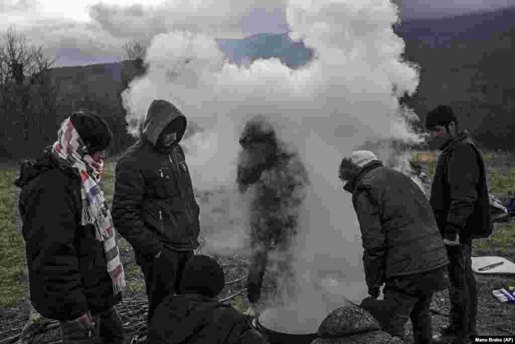 Një grup refugjatësh nga Afganistani gatuajnë në malet përreth qytetit Bihaq të Bosnjës.