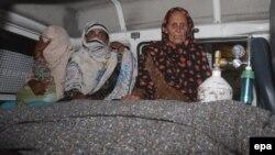 Таспен ұрып өлтірілген Фарзананың туыстары оның мәйітінің қасында отыр. Пәкістан, Лахор, 27 мамыр 2014 жыл.