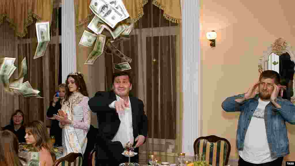 "Kadyrov (right) watches as a man tosses $100 bills at a restaurant in Gudermes during a celebration to honor the winner of the republic's first ""Beauty of Chechnya"" pageant in 2006."