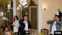 Ramzan Kadyrov (sağda) restoranda bu adamın 100 dollarlıq əskinasları necə artdığına tamaşa edir, 29 may 2006-cı il.