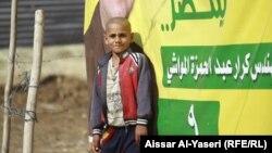 طفل أمام ملصق دعائي لمرشح في النجف