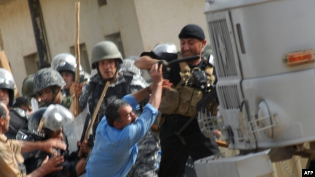 Iraqi police clash with exiled Iranian dissidents inside Camp Ashraf in 2009.