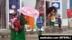 Школьники в Ашгабате проходят мимо продуктового магазина. Май 2020 года.
