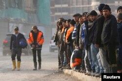 Рабочие ждут автобуса на строительной площадке. Сочи, 10 февраля 2013 года.