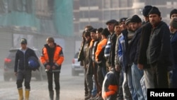 Soçide awtobusa garaşýan işçiler.10-njy fewarl, 2013.