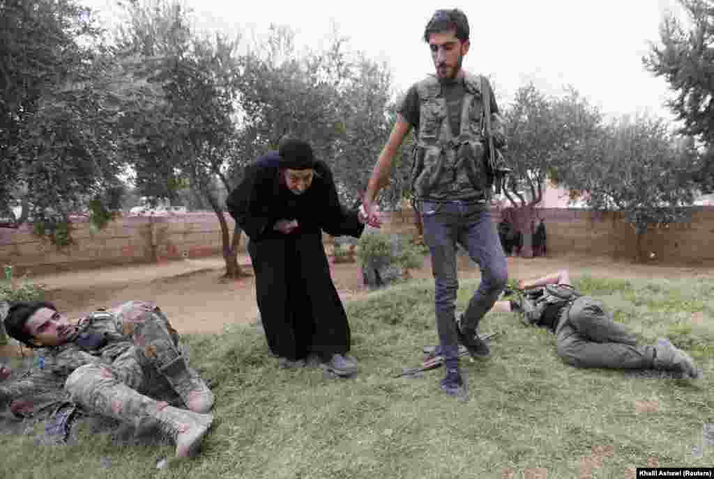 A Turkish-backed Syrian rebel fighter walks an elderly woman past fellow resting combatants near the border town of Tal Abyad on October 24. (Reuters/Khalil Ashawi)