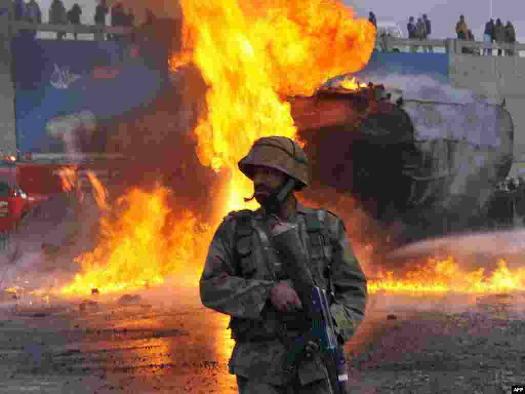 Пакістан, Пэшавар: пакістанскі жаўнер на фоне пажару ад нападу на нафтавую базу, што забясьпечвае палівам войскі NATO ў Аўганістане.