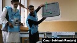 دو کارمند کمیسیون مستقل انتخابات در یکی از محلات رایگیری در کابل آرای ریخته شده در یک صندوق را شمارش میکنند