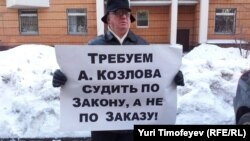 A man in front of a Moscow court protests the prosecution of entrepreneur Aleksei Kozlov.