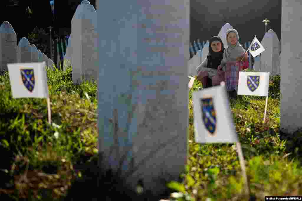 A woman and child are pictured on June 10, 2015 at the Potocari memorial for victims of the 1995 massacre in Srebrenica, Bosnia-Herzegovina.  During the 1992-95 war in Bosnia, the United Nations set aside Srebrenica as a safe haven for civilians. But on July 11, 1995, Bosnian Serb troops overran the town and killed about 8,000 Muslim men and boys in the ensuing days. (RFE/RL, Midhat Poturovic)