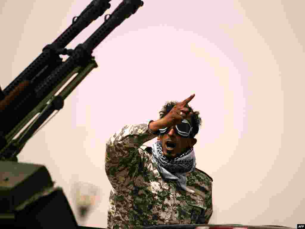 A Libyan rebel gestures as he mans an antiaircraft gun in Ajdabiyah on March 14, as Libyan strongman Muammar Qaddafi's forces shelled rebel positions on the doorstep of the key town, which the revolt against his rule has vowed to defend at all costs. Photo by Patrick Baz for AFP