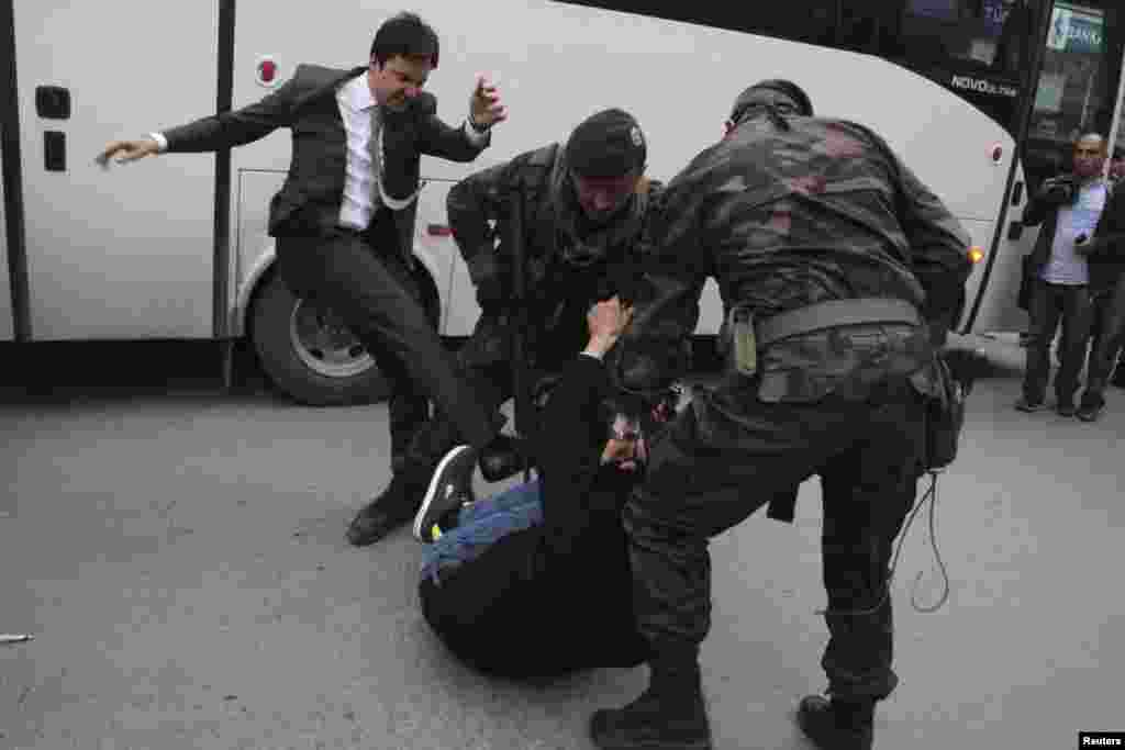 As police officers detain him, a protester is kicked by Yusuf Yerkel (left), advisor to Prime Minister Tayyip Erdogan, during a protest against Erdogan's visit to Soma, a district in western province of Manisa, where hundreds of miners died in an explosion this week. (Reuters/Mehmet Emin)