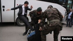 Turkey -- A protester is kicked by Yusuf Yerkel (L), advisor to Prime Minister Tayyip Erdogan, as Special Forces police officers detain him during a protest against Erdogan's visit to Soma, a district in western province of Manisa, May 14, 2014