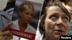 Një protestuese mban foton e ish-kryeministres ukrainase, Julia Timoshenko gjatë protestave të mëparshme kundër gjykimit të saj