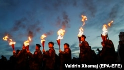Kosovar Albanians hold torches to mark the 20th anniversary of the death of KLA commander Adem Jashari in the village of Prekaz on March 7.