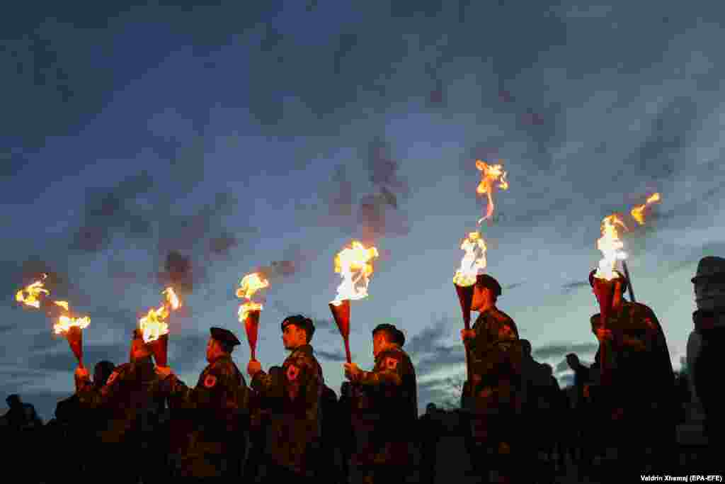 Kosovar Albanians in military costumes hold torches during a bonfire night to mark the 20th anniversary of  the death of Kosovo Liberation Army (UCK) Commander Adem Jashari on March 7. (epa-EFE/Valdrin Xhema)