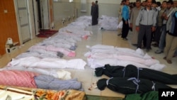 A handout picture released by the Syrian opposition's Shaam News Network shows the shrouded bodies of 92 people, including 32 children, before their burial in the town of Houla on May 26.