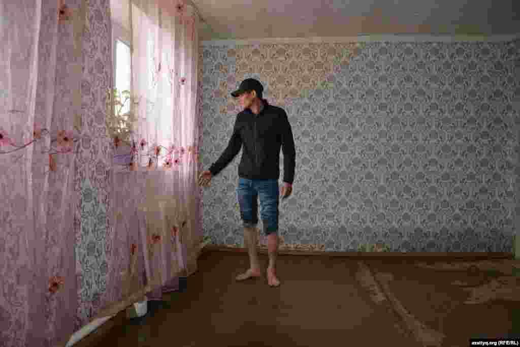 Житель села показывает свой дом, пострадавший из-за паводка.