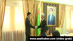 Представитель Центральной комиссии по выборам и проведению референдумов Туркменистана поздравляет Сердара Бердымухамедова с победой на довыборах. Скриншот программы, показанной в эфире государственного телевидения.