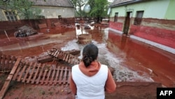 A woman looks at the damage in Devecser, Hungary, on October 5.