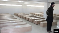 A Pakistani security official stands guard beside coffins containing the remains of the victims of plane crash at a hospital in Abbottabad on December 8.