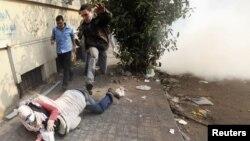 Демонстранти бегаат од солзавец во Каиро.