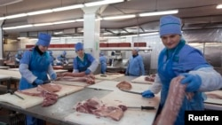 Belarusian workers prepare meat at a processing plant in Brest.