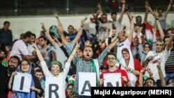 Iranian football fans in Tehran watching Iran-Spain game on large screens.