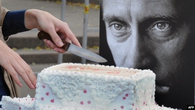A pro-Kremlin activist cuts a birthday cake for Putin in Moscow.