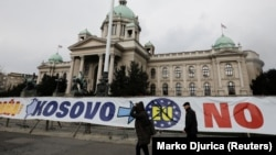 People walk past the Serbian parliament building in central Belgrade.