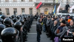 Police stand guard in front of protesters during a demonstration in support of EU integration in front of the parliament building in Kyiv on December 3.