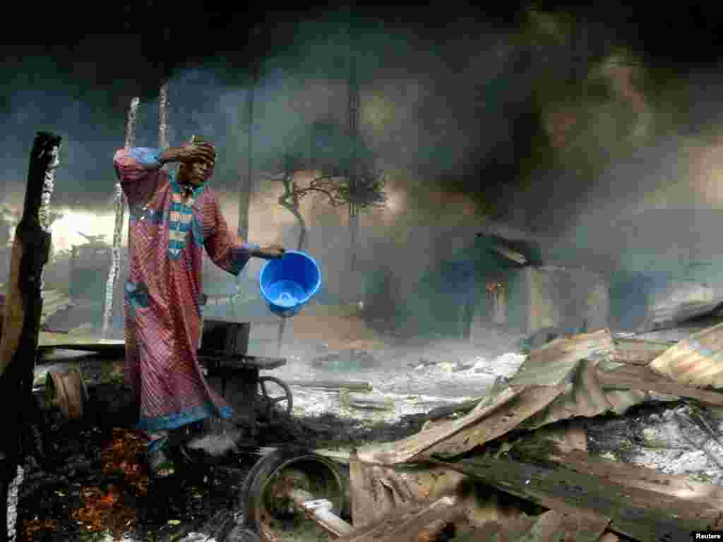A man rinses soot from his face at the scene of a gas pipeline explosion near Nigeria's commercial capital Lagos December 26, 2006. Up to 500 people were burned alive on Tuesday when fuel from a vandalised pipeline exploded in Nigeria's largest city, Lagos, emergency workers said. Hundreds of residents of the Abule Egba district went to scoop fuel using plastic containers after thieves punctured the underground pipeline overnight to siphon fuel into a road tanker, locals said. REUTERS/Akintunde Akinleye