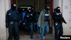Полицейские на выходе из дома, охваченного рейдом в Берлине. 16 января 2015 года.