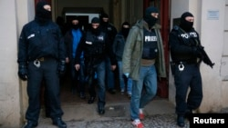 Полиция арнайы жасағы терроризм күдігімен тексеру жүргізген үйден шығып келеді. Берлин, 16 қаңтар 2015 жыл.