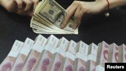 Пачки банкнот номиналом 100 юаней и доллары США. Иллюстративное фото.