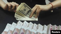 An employee counts U.S. dollars next to Renminbi yuan banknotes at a bank in Anhui Province in September.