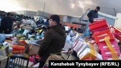Барахолкадағы «Құлагер» базарындағы өрттен жүктерін шығарып жатқан адамдар. Алматы, 17 қараша 2013 жыл.