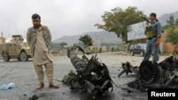 FILE: A policeman and a civilian stand at the site of a bomb attack outside the government of Parwan province in Charikar