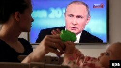 A Russian woman plays with her baby while watching President Vladimir Putin annual televised call-in earlier this year.