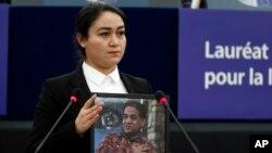Jewher Ilham ține în mâini o fotografie a tatălui său