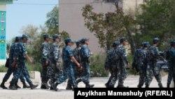 Полицейлер соты өтіп жатқан ғимарат маңында жүрген сарбаздар. Ақтау, 3 мамыр 2012 жыл. (Көрнекі сурет)