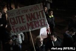 """СИРИЗА белсенділері """"Фрау Меркель, тыныш ұйықтауыңа тілектеспіз, бірақ біз шынымен билікке келдік"""" деген плакат көтеріп барады. Грекия, Афин, 26 қаңтар 2015 жыл."""
