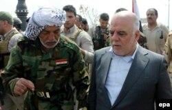 نخستوزیر عراق، همراه یک شبهنظامی شیعه در تکریت. در آغاز عملیات برای بازپسگیری تکریت، نزدیک به ۱۸۰۰۰ شبه نظامی در قالب نیروهای بسیج مردمی و ۳۰۰۰ نفر از نظامیان عراقی حضور داشتند.
